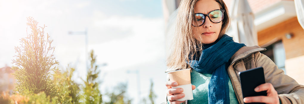 Woman sitting outside wearing glasses on her smartphone